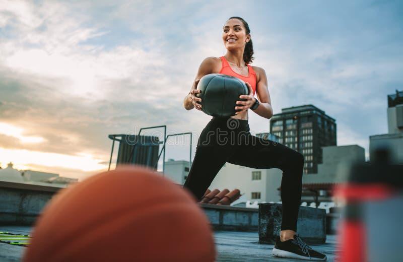 Eignungsfrau, die Training unter Verwendung eines Medizinballs tut stockfotos