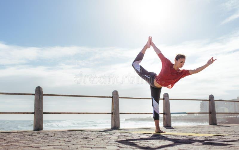 Eignungsfrau, die Yoga Natarajasana-Haltung tut stockbild
