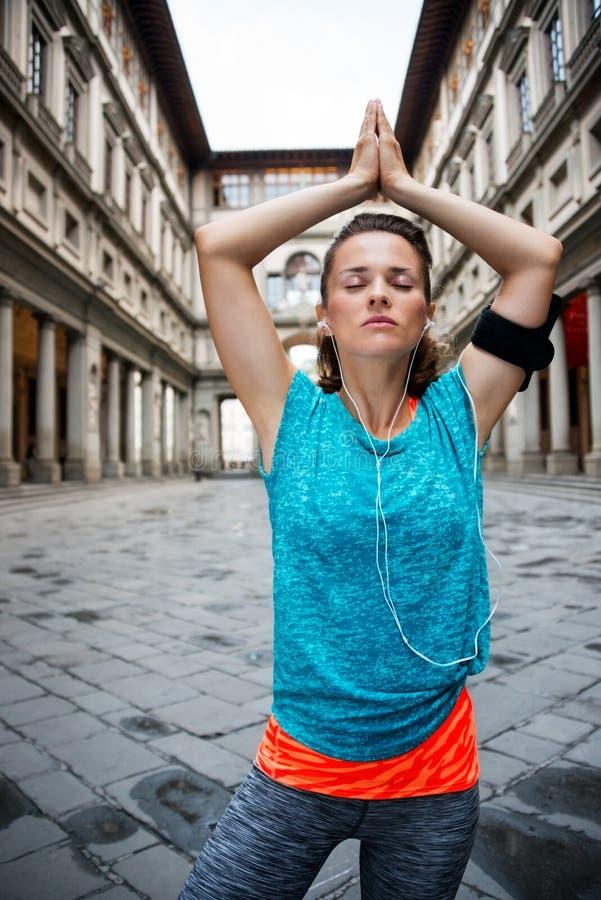 Eignungsfrau mit den Kopfhörern, die draußen Yoga tun Florenz lizenzfreie stockfotos