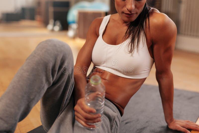 Eignungsfrau mit Wasserflasche an der Turnhalle lizenzfreie stockbilder