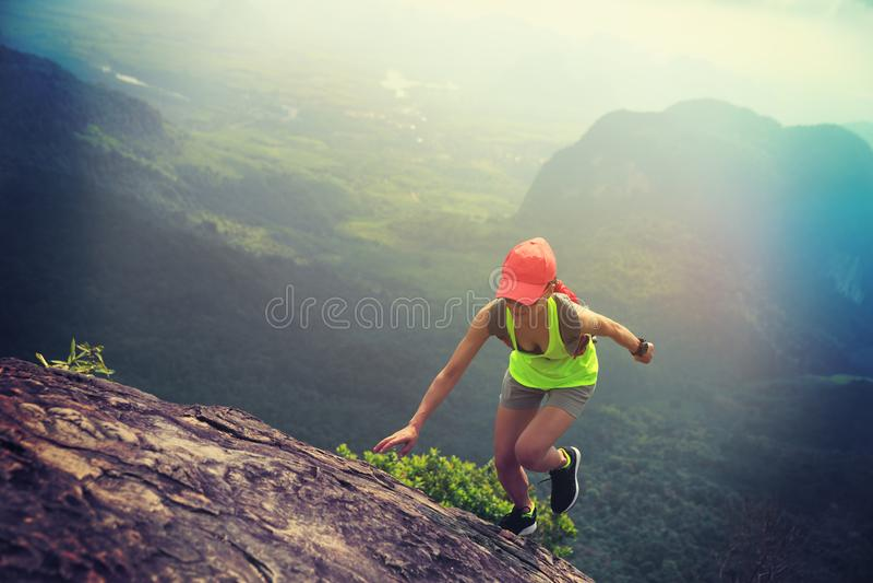Eignungsfrauenhinterläufer, der bis zur Gebirgsspitze läuft stockbild