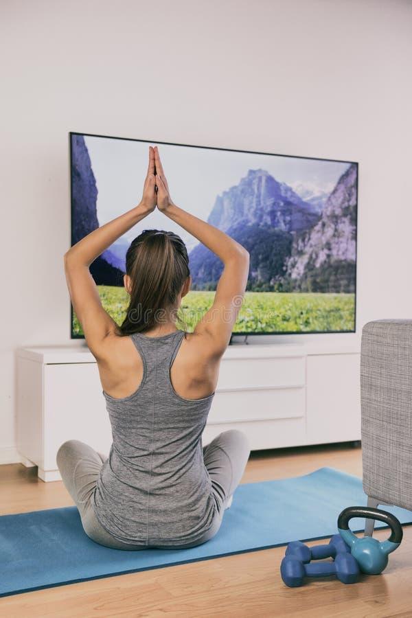 Eignungsklasse des Yoga zu Hause, die im Fernsehen Appon-line-Frauentraining im Wohnzimmer auf der Übungsmatte allein meditiert - lizenzfreies stockbild