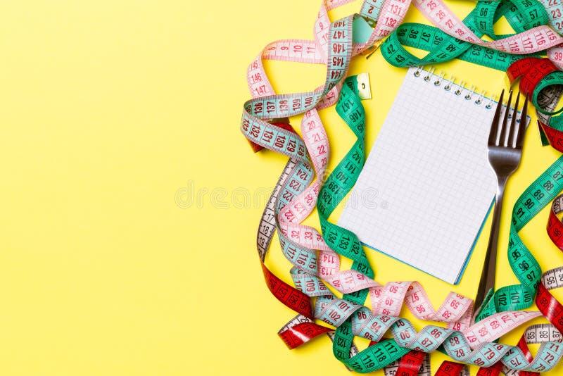 Eignungskonzept mit leerem Raum für Ihren Entwurf auf gelbem Hintergrund Draufsicht des Notizblockes und der Gabel umgeben mit bu lizenzfreie stockfotografie
