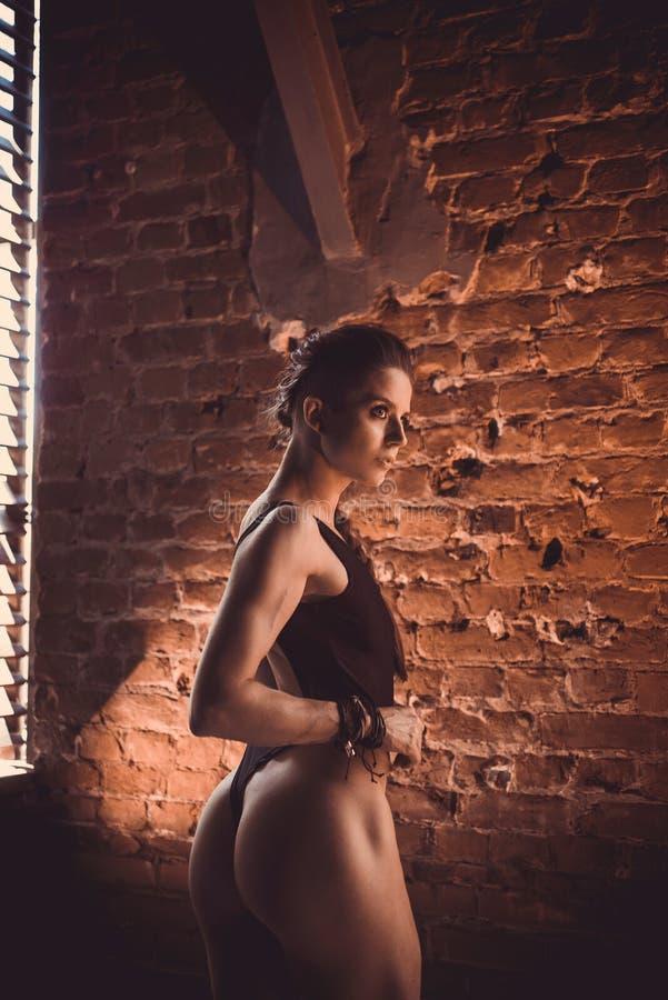 Eignungskrafttraining-Trainingskonzept - sexy Sportmädchen des muskulösen Bodybuilders, das Übungen in der Turnhalle tut lizenzfreies stockbild