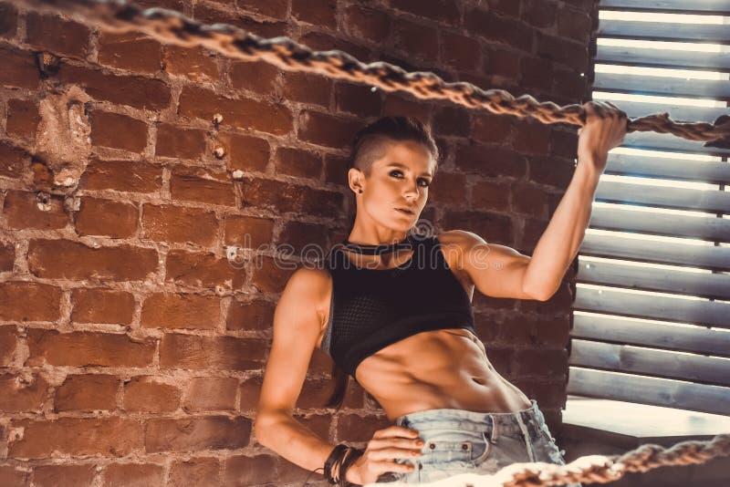 Eignungskrafttraining-Trainingskonzept - sexy Sportmädchen des muskulösen Bodybuilders, das Übungen in der Turnhalle tut lizenzfreie stockfotografie