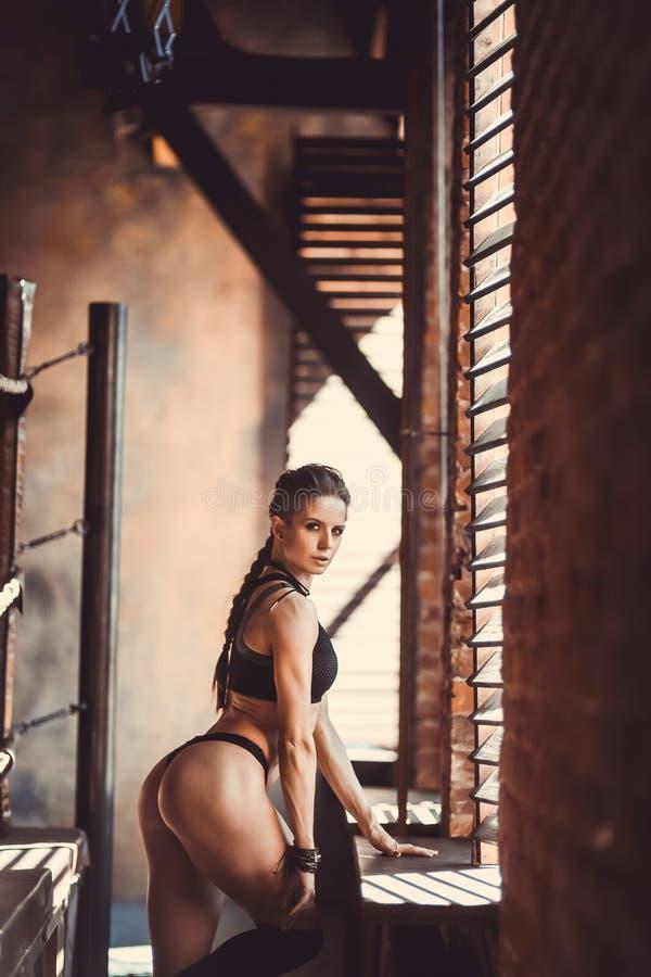 Eignungskrafttraining-Trainingskonzept - sexy Sportmädchen des muskulösen Bodybuilders, das Übungen in der Turnhalle tut stockbild