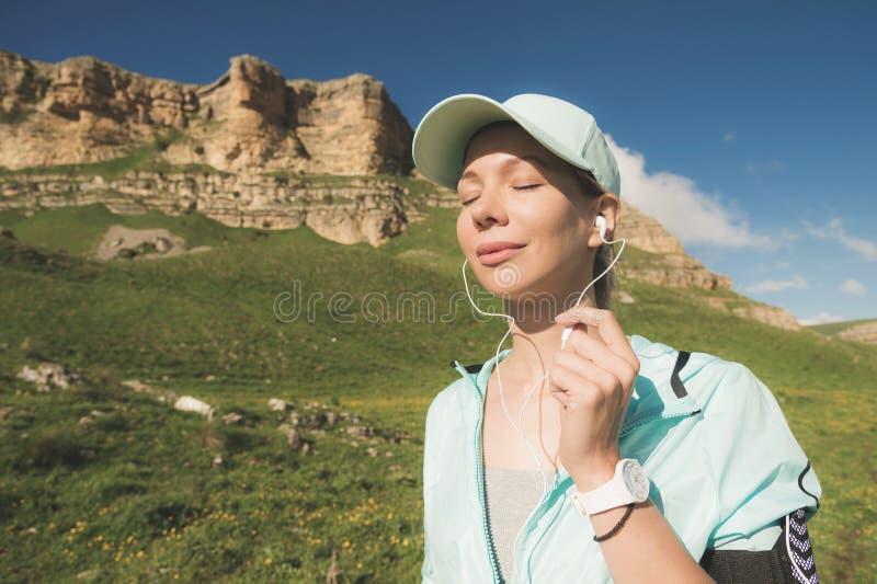 Eignungsläuferfrau, die seine Augen hören Musik auf der Natur schließt Porträt von tragenden Kopfhörern des schönen Mädchens stockfotografie