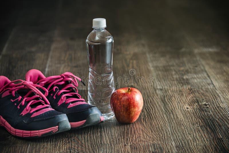 Eignungslaufsportartenausrüstung, Turnschuhe wässern den Apfel, gesund lizenzfreies stockfoto