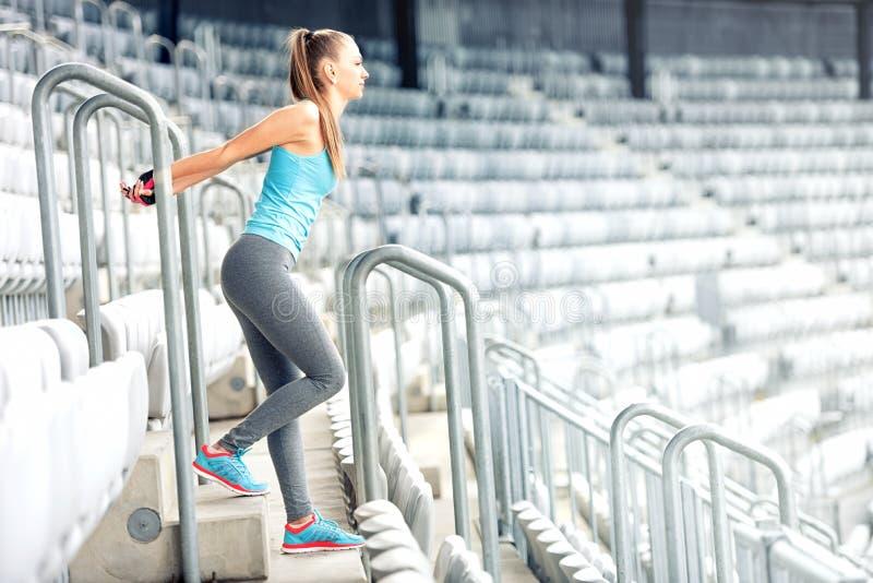 Eignungsmädchen, das Eignungsübungen tut und auf Stadionstreppe ausarbeitet Rüttler auf Morgentraining, gesundes Lebensstilkonzep stockfoto