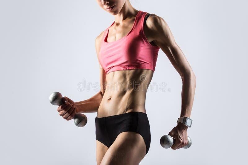 Eignungsmädchen, das mit Gewichten trainiert stockfoto
