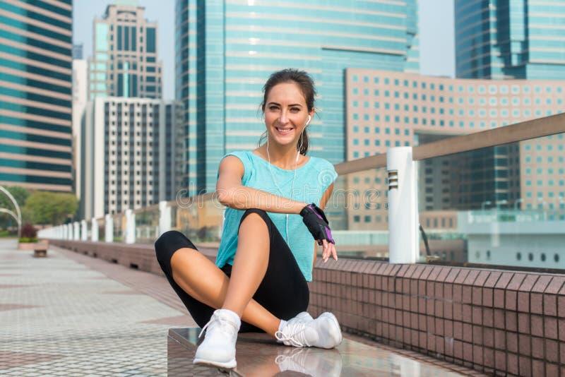 Eignungsmädchen, das nach der Trainingssitzung sitzt auf Bank in der Stadtgasse sich entspannt Junge athletische Frau, die Pause  stockfotografie