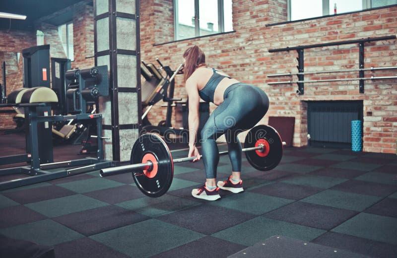Eignungsmädchen mit der Sportkleidung, die deadlift tut stockbild