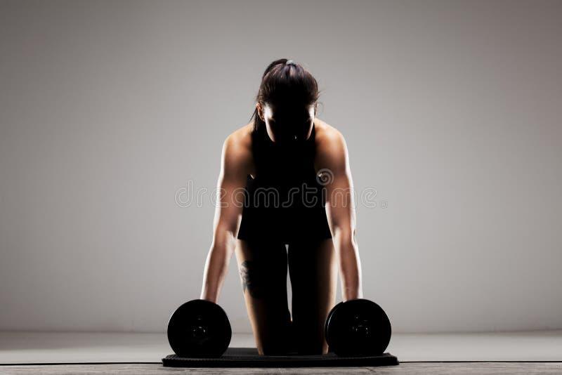 Eignungsmädchen, welches das Handeln drückt, ups mit Gewichten halbes Schattenbild lizenzfreies stockfoto