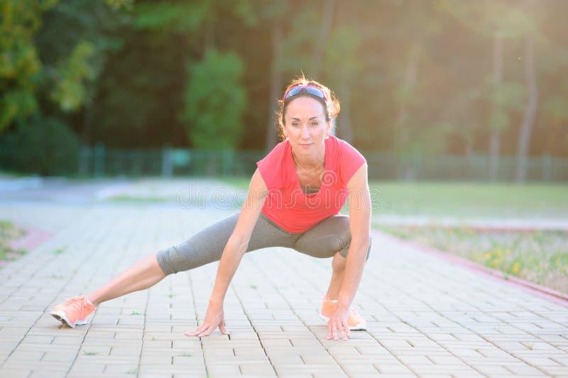 Eignungsmädchenläufer, der Beine vor Lauf ausdehnt stockbilder