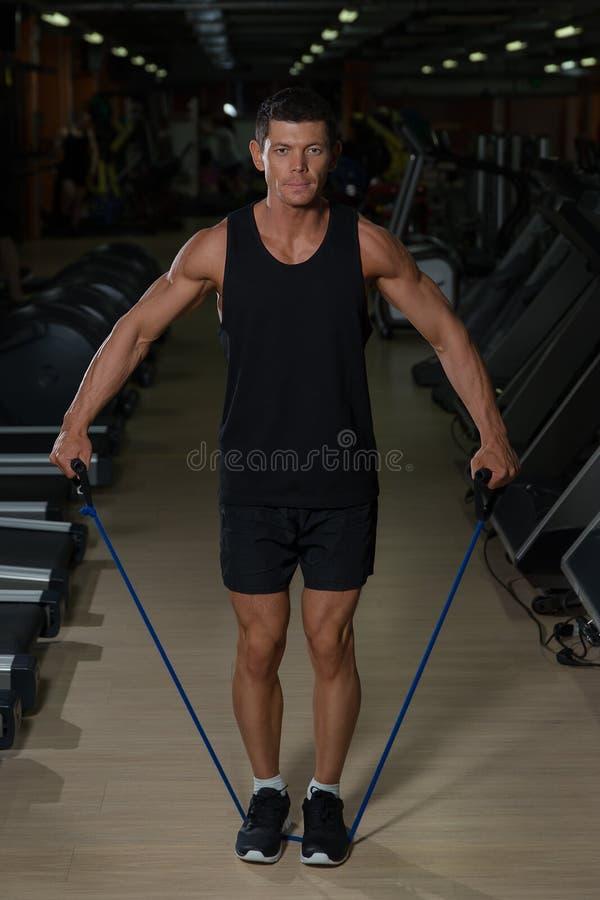 Eignungsmann, der mit dem Ausdehnen des Bandes in der Turnhalle trainiert Muskulöser Sport bemannt das Trainieren mit elastischem stockfoto