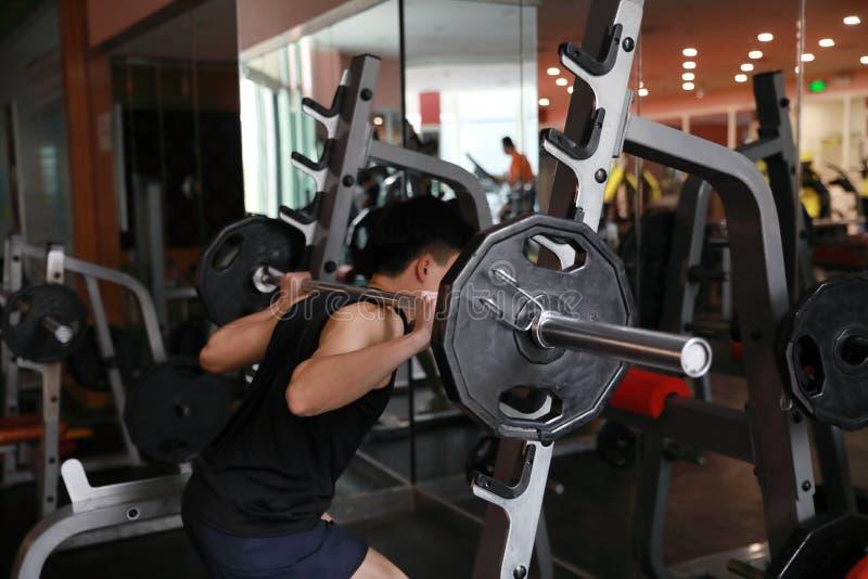 Eignungsmann in der Turnhalle, die Hocke tut Mann mit Dumbbellgewicht-Ausbildungsanlagegymnastik Innen, Lehrer lizenzfreie stockbilder