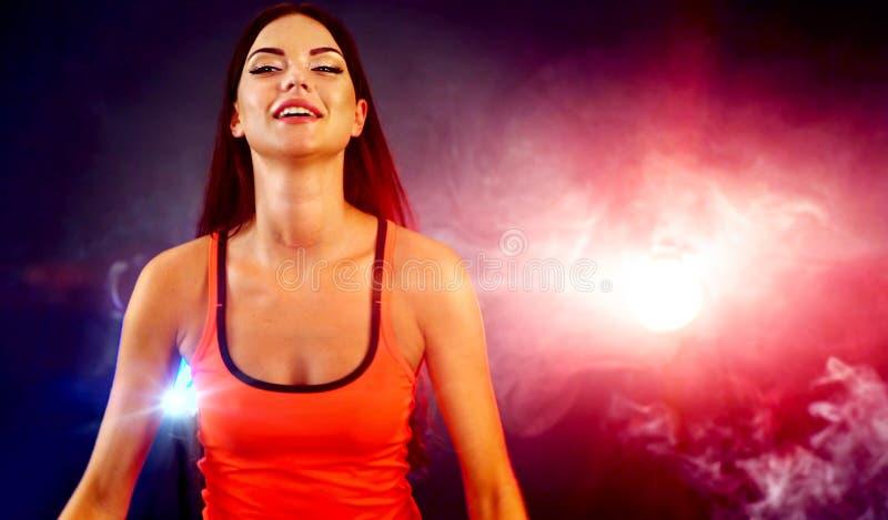 Eignungstrainer-Aerobicfrau, die in der Turnhalle mit trainiert stockfotos