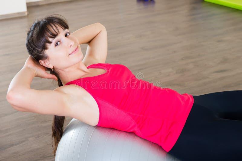 Eignungstraining der jungen Frau in der Turnhalle mit fitball lizenzfreie stockfotos