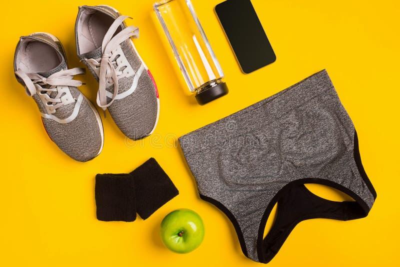 Eignungszubehör auf einem gelben Hintergrund Turnschuhe, Flasche der intelligenter und des Sports Spitze des Wassers, stockbild