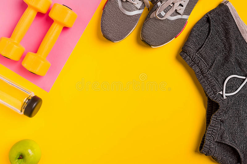 Eignungszubehör auf einem gelben Hintergrund Turnschuhe, Flasche Wasser, Apfel und Dummköpfe stockbild