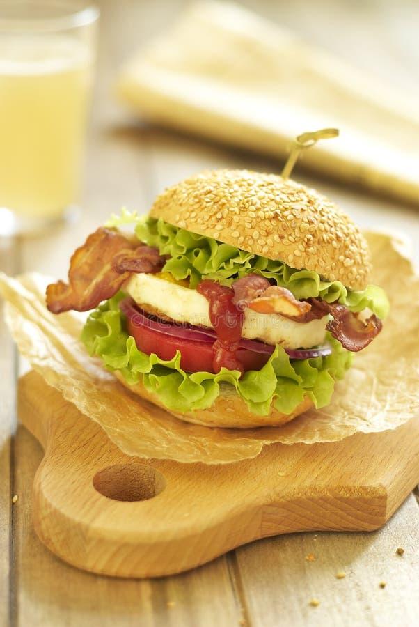 Eihamburger met tomaat, salade, onuion en bacon stock afbeelding