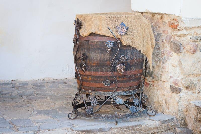 Eiken wijnvat met ijzerringen en druif op steen oude muur stock afbeelding