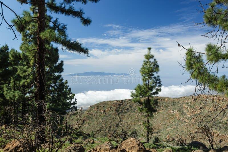Eiland die van die La Gomera, over de horizon stijgen, gedeeltelijk door de wolken wordt behandeld Heldere blauwe hemel De sporen stock foto's