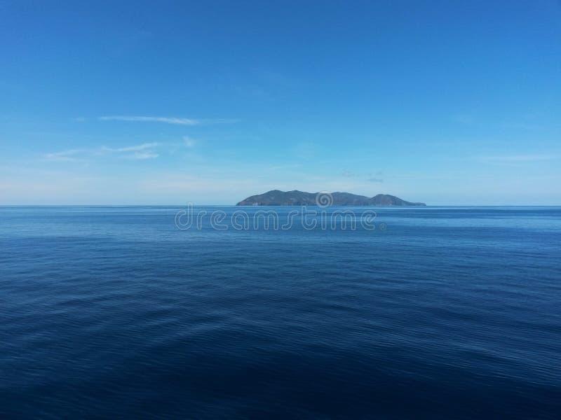 Eiland op de horizon onder de blauwe hemel stock fotografie
