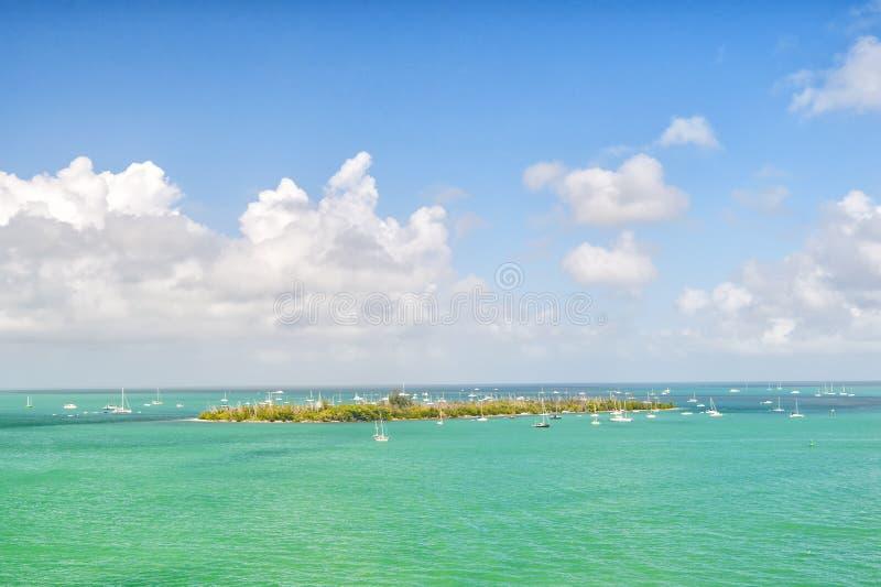 Eilandenland en zeilboten in turkooise overzees in het zeer belangrijke westen, de V.S. Zeegezicht met varende boten op bewolkte  royalty-vrije stock fotografie