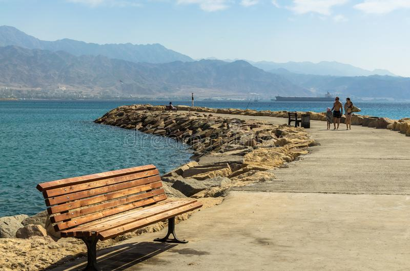 EILAT, ISRAEL – November 7, 2017: new walking stone harbor`s pier is equipped with the wooden benches royalty free stock photos