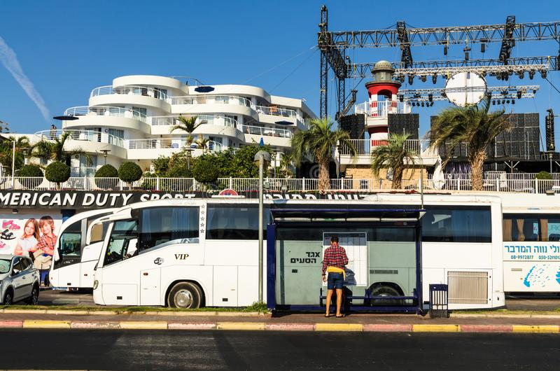 EILAT, ISRAEL – November 7, 2017: Tourist, studying the bus schedule, Eilat street, Israel. EILAT, ISRAEL – November 7, 2017: In the foreground royalty free stock photo