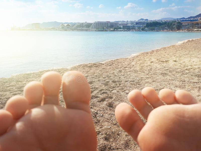 Eilat, Israel beach and sea view through feet fingers. At the beach. View through female feet fingers. Eilat, Israel royalty free stock images