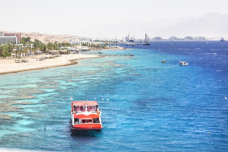EILAT, ISRAEL - JUNE 14, 2014: Redboat with tourists at sea in the bay of Eilat, Israel. EILAT, ISRAEL - JUNE 14, 2014: Red boat with tourists at sea in the bay stock photos