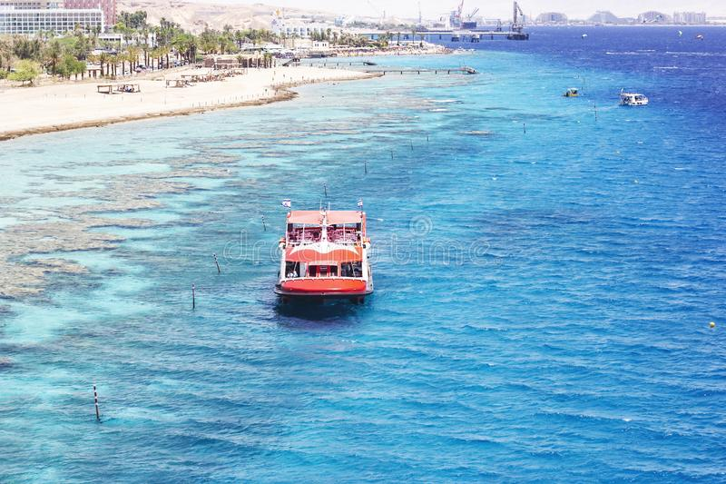 EILAT, ISRAEL - JUNE 14, 2014: Redboat with tourists at sea in the bay of Eilat, Israel. EILAT, ISRAEL - JUNE 14, 2014: Red boat with tourists at sea in the bay stock photography
