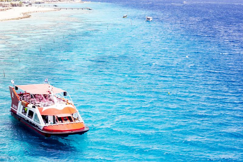EILAT, ISRAEL - JUNE 14, 2014: Redboat with tourists at sea in the bay of Eilat, Israel. EILAT, ISRAEL - JUNE 14, 2014: Red boat with tourists at sea in the bay stock image