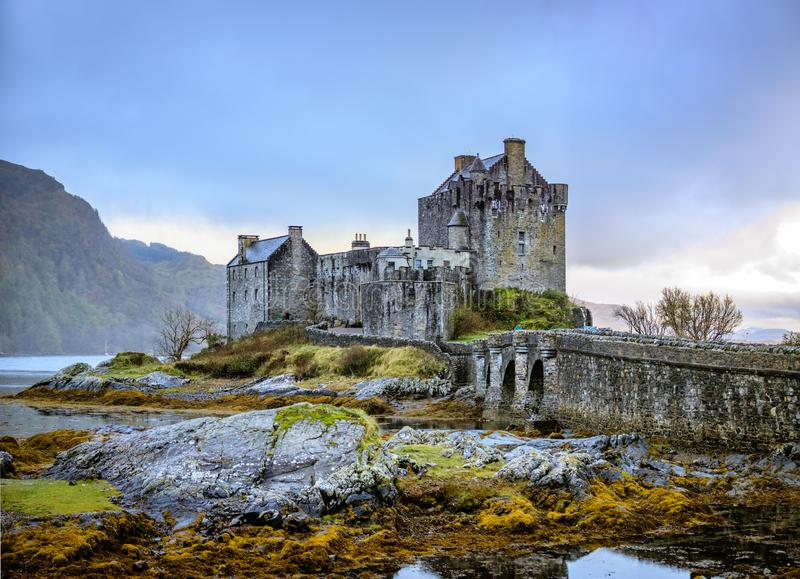 Eilean Donan Castle with brooding sky and mossy covered rocks in the foreground in Highland, Scotland UK royalty free stock photography