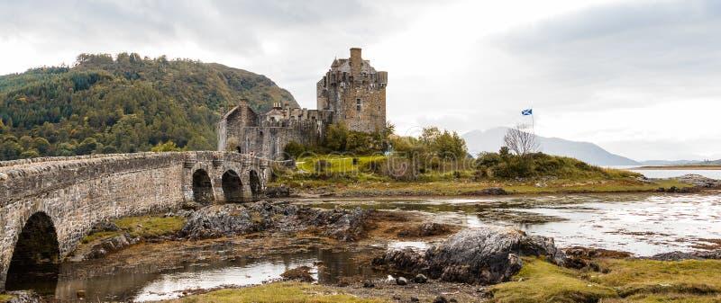 Panorama of Eilean Donan castle with Scottish flag. EILEAN DONAN CASTLE, DORNIE, SCOTLAND - SEPTEMBER 20, 2014: panorama from the bridge with Scottish flag royalty free stock images