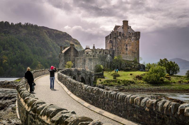 Eilean Donan castle. Scottish landscape. Scotland, Great Britain. Eilean Donan medieval castle, stone bridge. People looking at the castle. Scottish landscape stock image