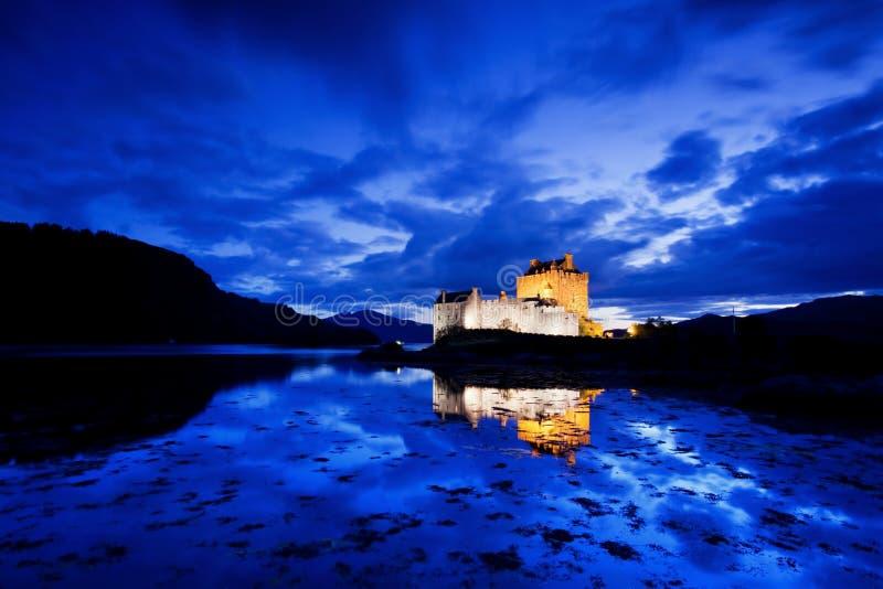 Eilean Donan Castle tijdens blauw uur na zonsondergang Het wijzen van op in het water tijdens avond, Loch Duich, Dornie, Schotlan stock afbeelding