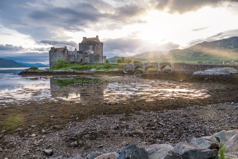 Eilean Donan kasztel podczas zmierzchu podczas gdy czółna przechodzi obok - Dornie, Szkocja zdjęcia royalty free