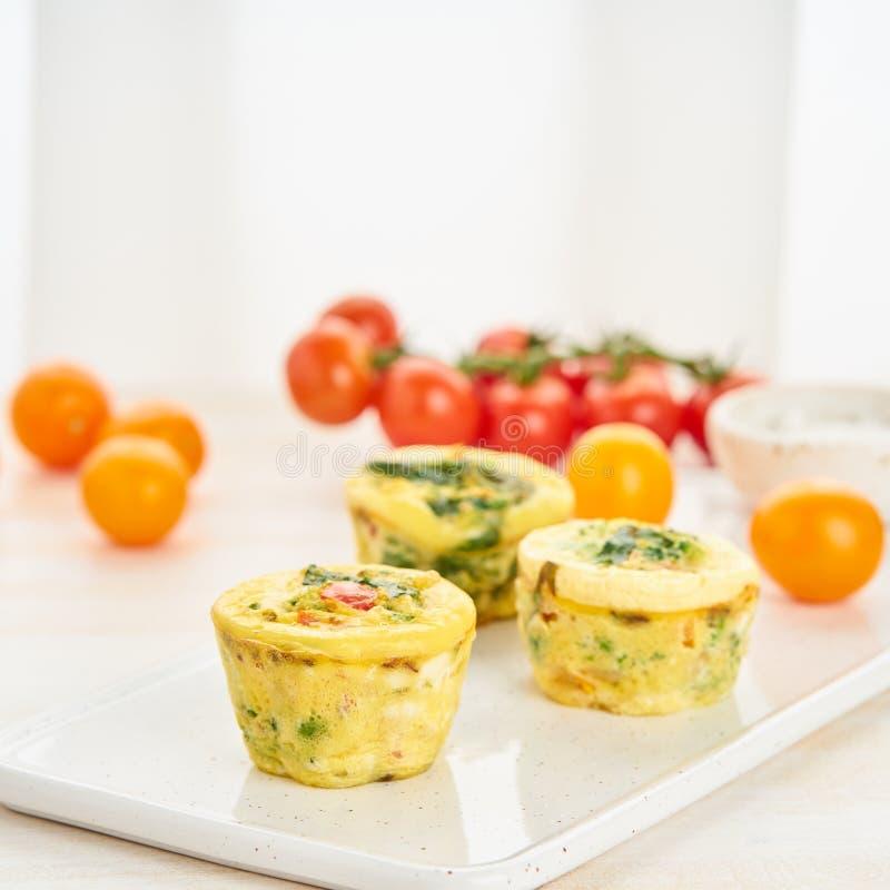 Eimuffins, paleo, Keton-Diät Omelett mit Spinat, Gemüse, Tomaten gebacken in den kleinen Formen, Seitenansicht stockfotografie