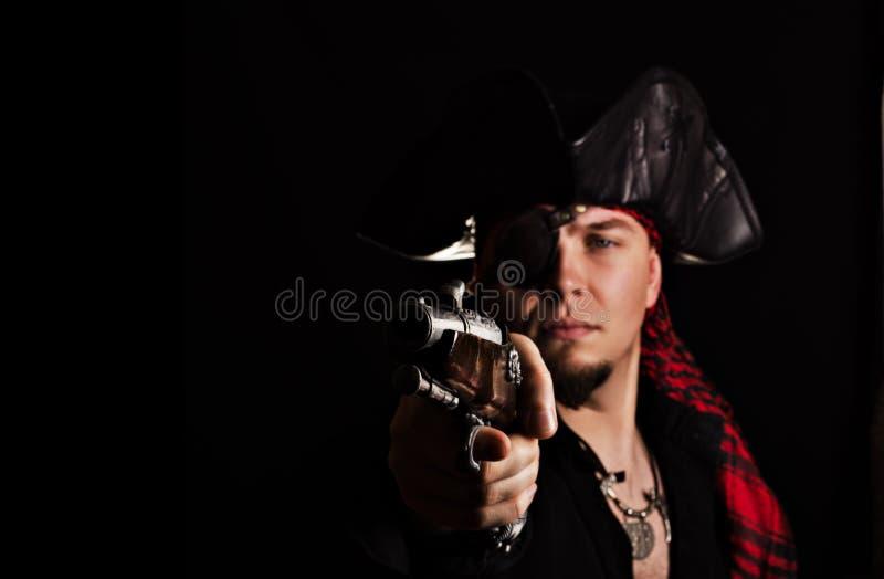Einäugiger junger Pirat zielt eine alte Pistole lizenzfreie stockfotos