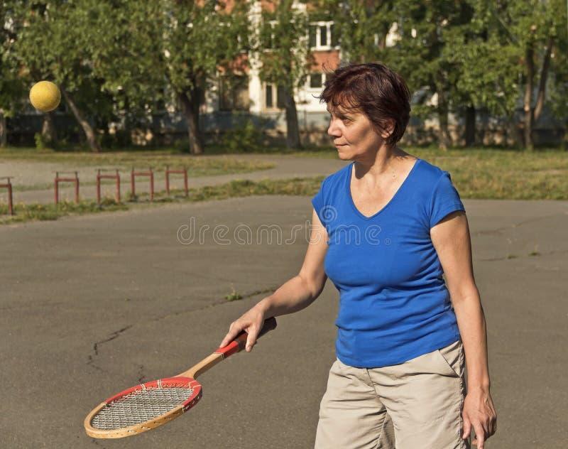 Ein älterer Athlet bildet mit einem Schläger und einem Tennisball aus stockfoto