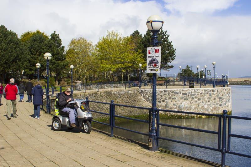 Ein älterer Bürger mit 94 Jährigen heraus und ungefähr auf einem Unfähigkeitsroller an der Seeseite in Bangor Nordirland lizenzfreie stockfotos