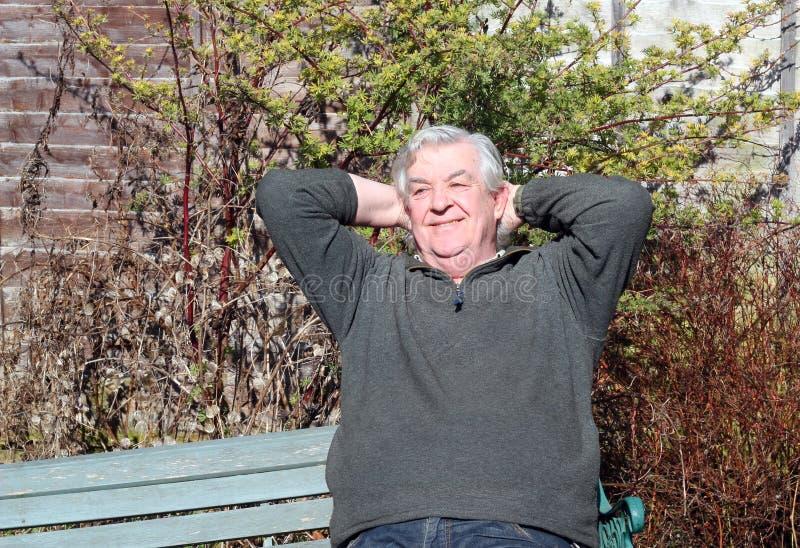 Mann, der mit den Händen hinter Kopf sich entspannt. stockbilder