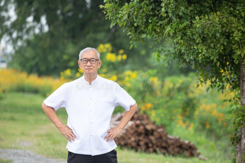 Ein älterer Mann, der morgens Übungen im Garten macht stockfotografie