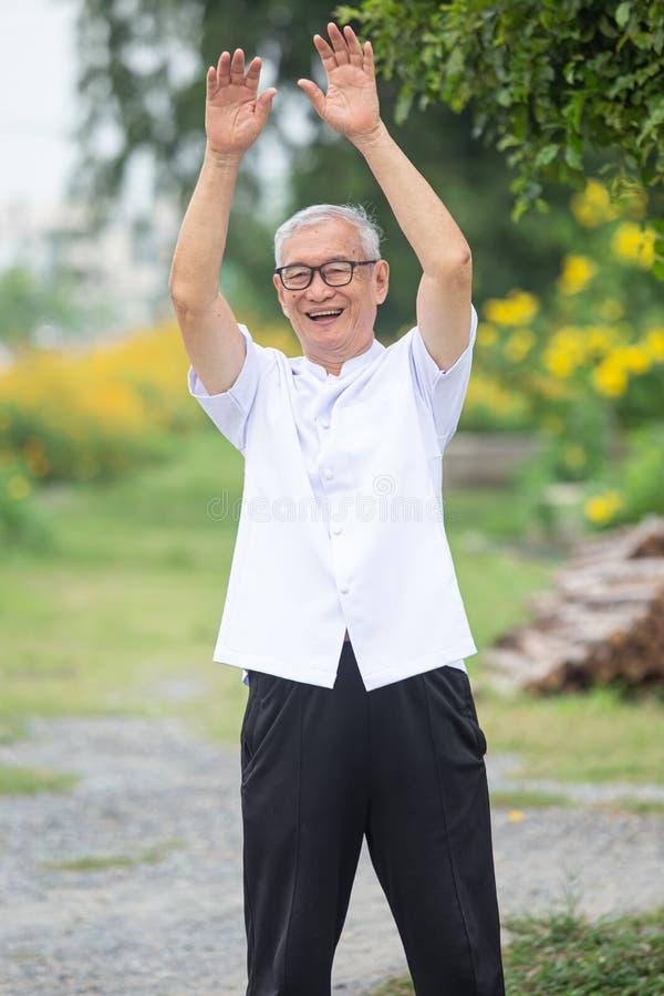 Ein älterer Mann, der morgens Übungen im Garten macht stockfoto