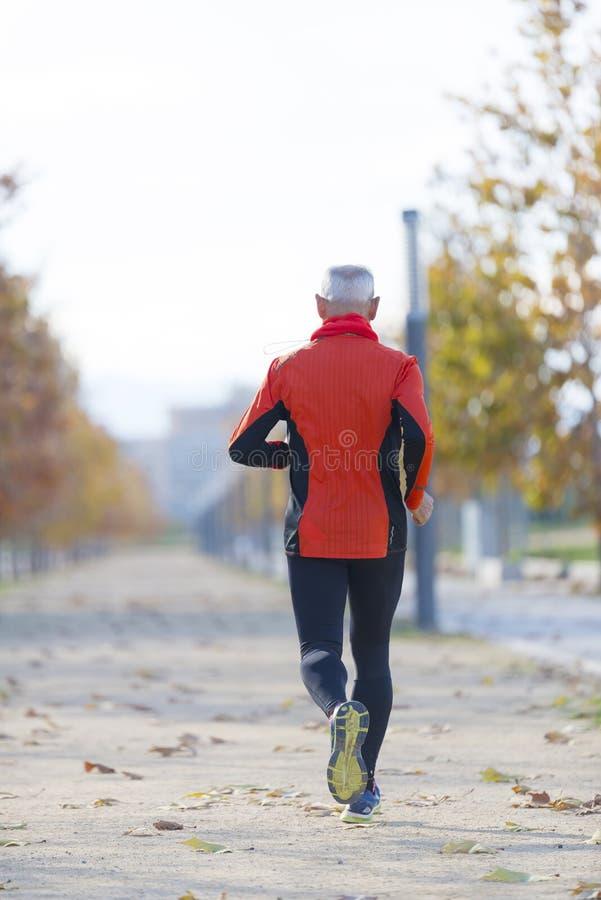 Ein älterer Mann, der in Schwarzem und in Orange gekleidet wird, läuft in den Park lizenzfreie stockfotografie