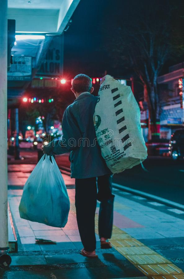 Ein älterer Mann geht, während er Taschen mit Waren in der Straße der Stadt nachts trägt lizenzfreies stockbild