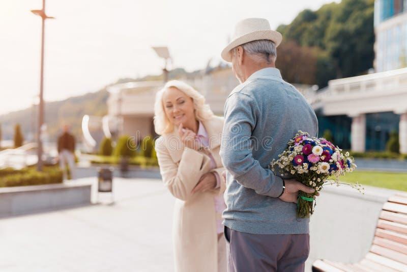 Ein älterer Mann hält einen Blumenstrauß von Blumen hinten zurück Eine Frau kam auf ein Datum und Versuche, auszuspionieren auf,  stockfotos